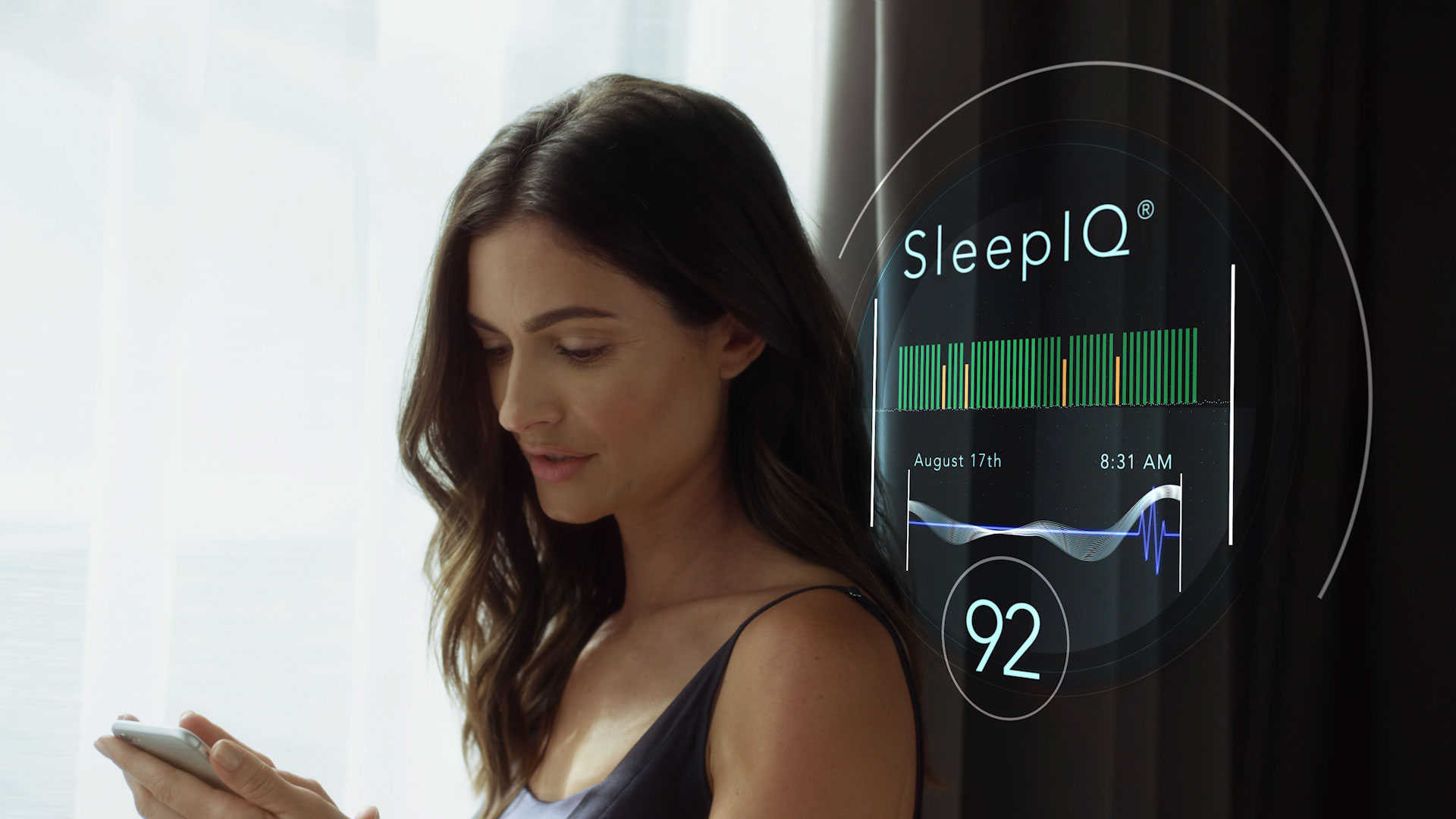 "Woman standing in front of a digital interface that reads ""Sleep IQ"" with the time and date, from the CES 2018 trade show"