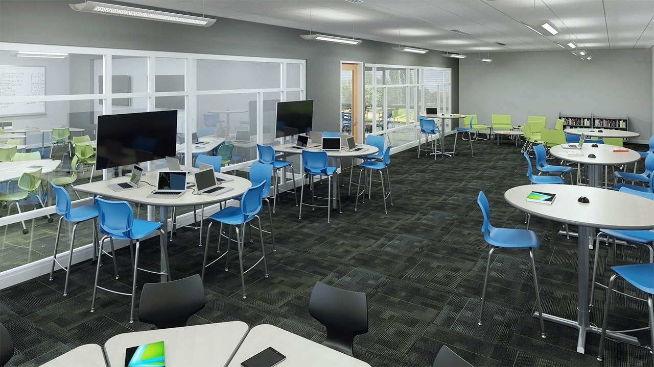 Tech classroom with dark flooring, tall circular tables, computer monitors, and blue chairs