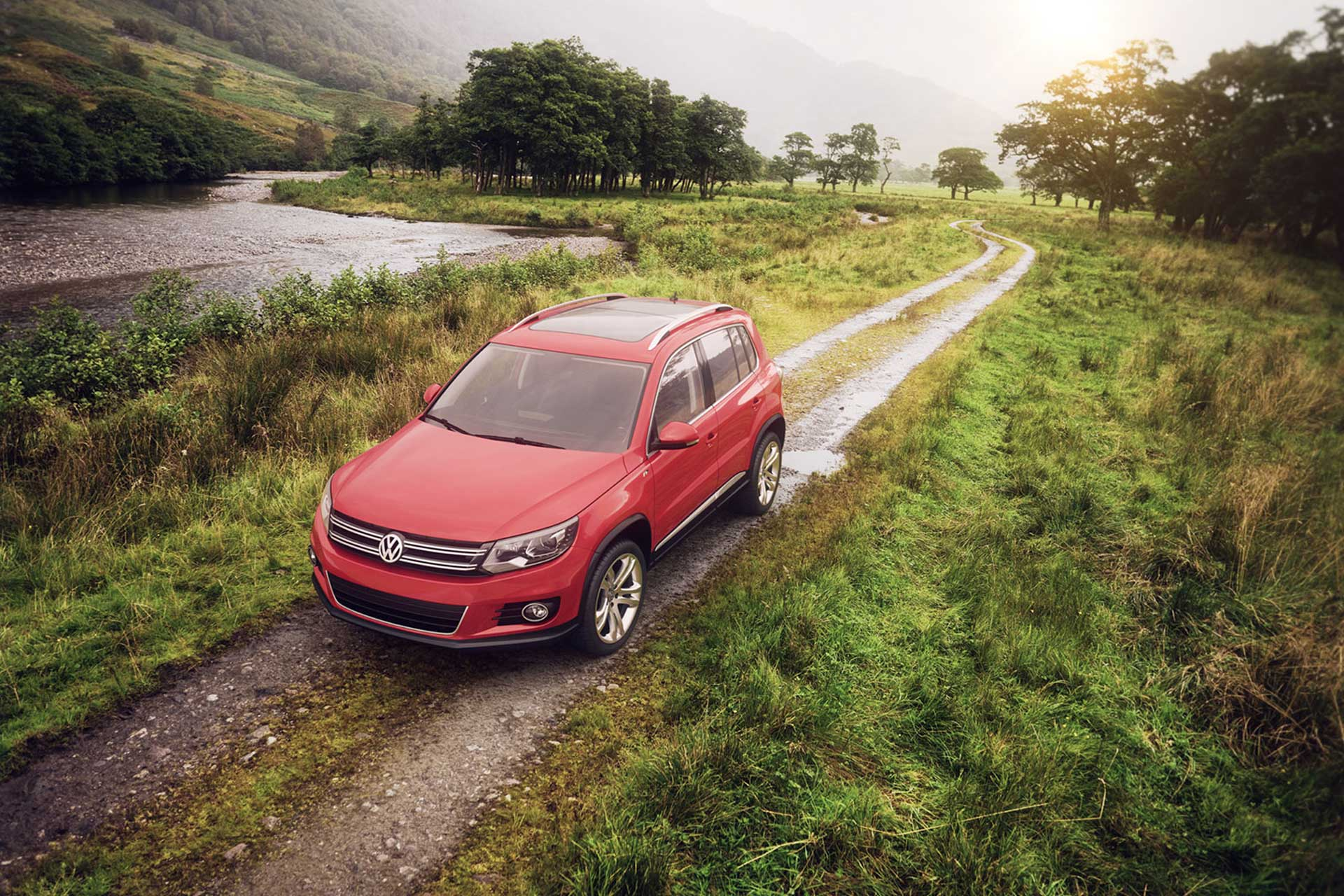Red Volkswagen Tiguan car driving down a gravel road in the country
