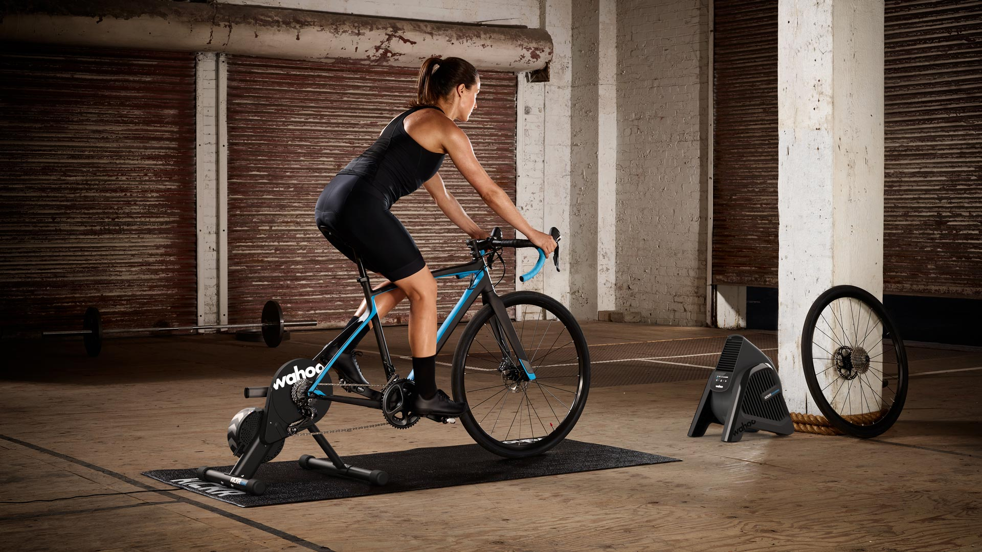 Wahoo product marketing image of a woman in athletic gear riding a stationary bike