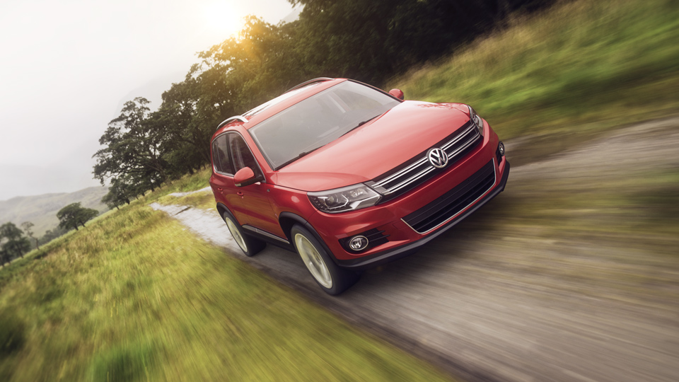 3D rendering of red VW Tiguan car on dirt road near green fields