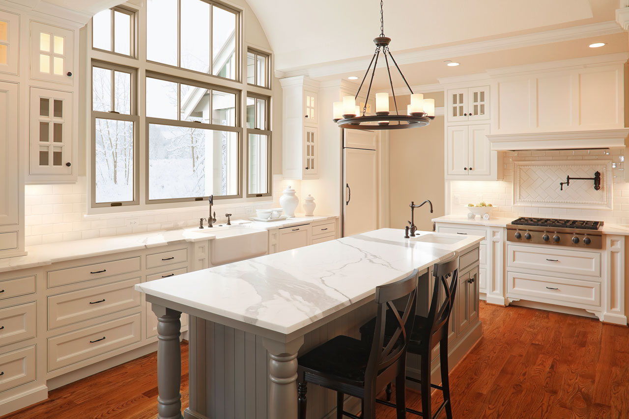 Beautifully lit kitchen with white counters and a view out the Renewal by Andersen windows