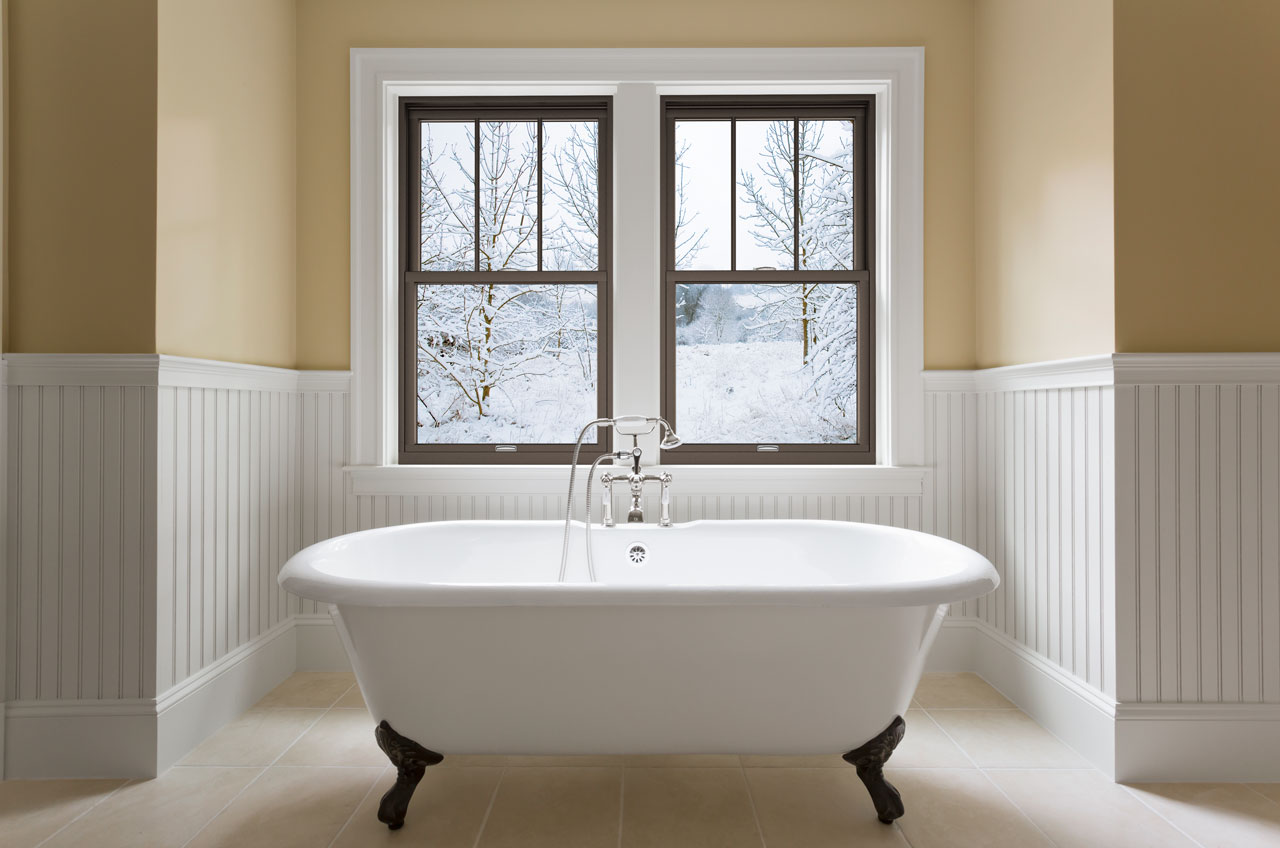 Claw-foot bathtub in front of large windows overlooking a snowy backyard