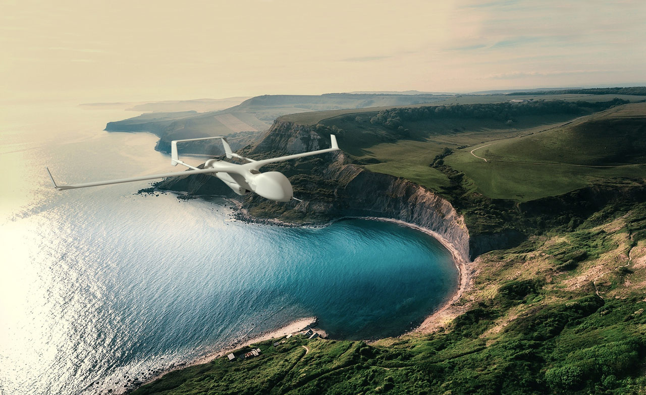 Gray Insitu Drone flying over a beach between a blue ocean and lush green hills