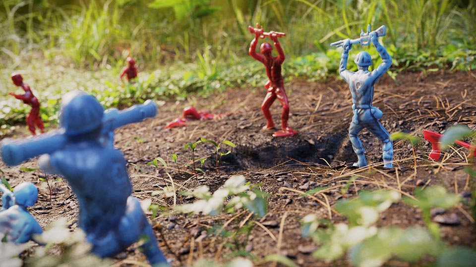 Blue and red army men toys in battle on dirt ground surrounded by grass and plants