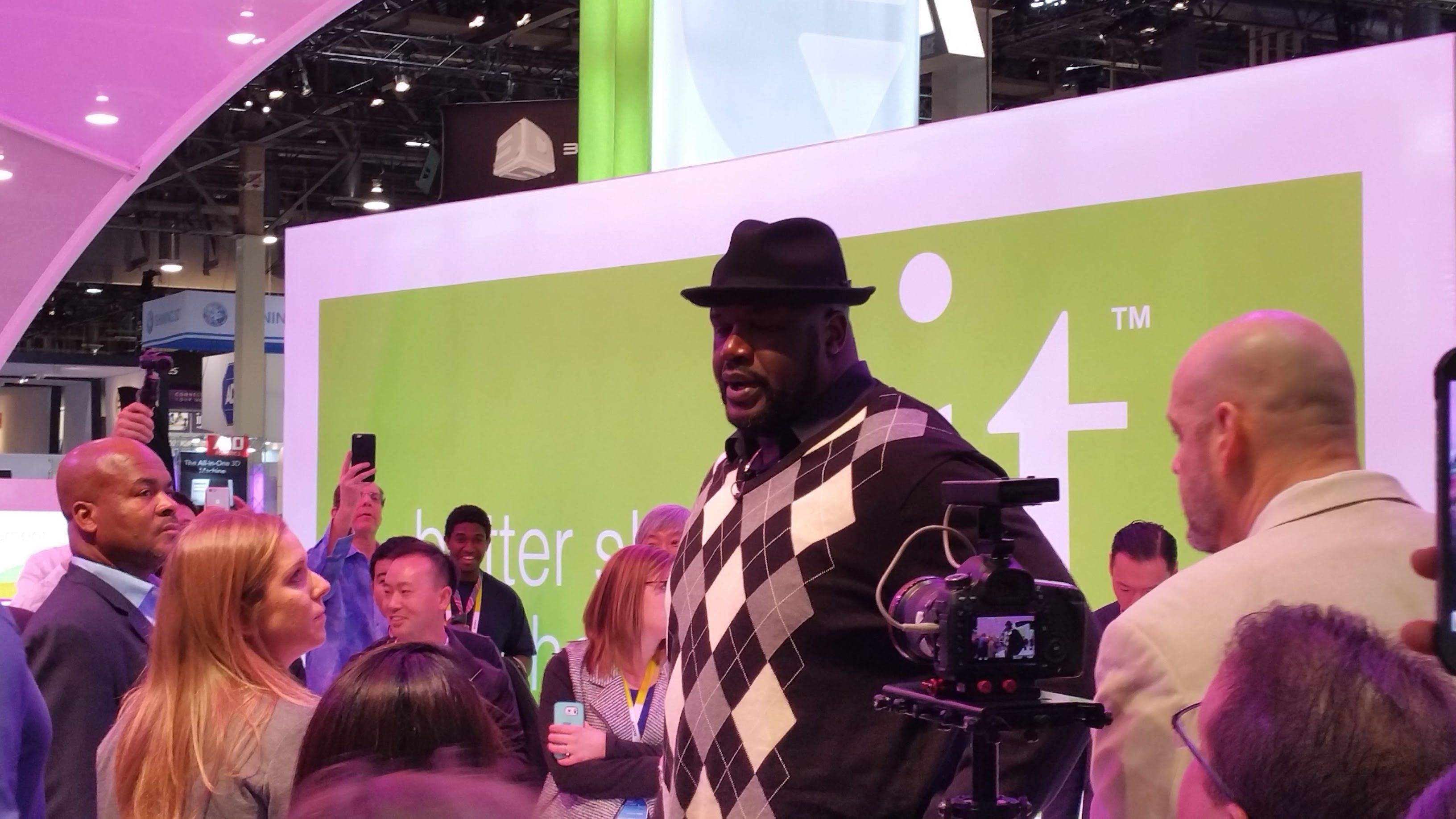 Shaq standing in a crowd in front of a green banner at CES 2016