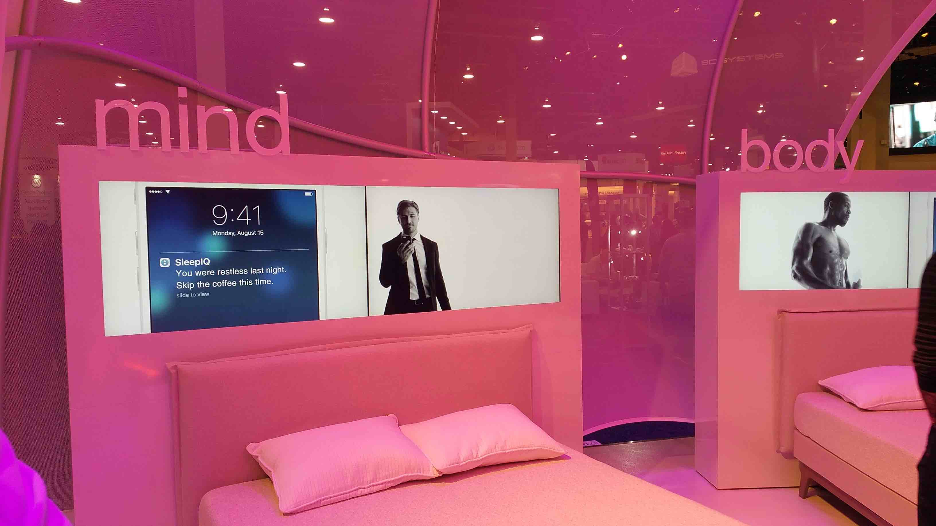 Pink-tinted tradeshow booth featuring smart beds