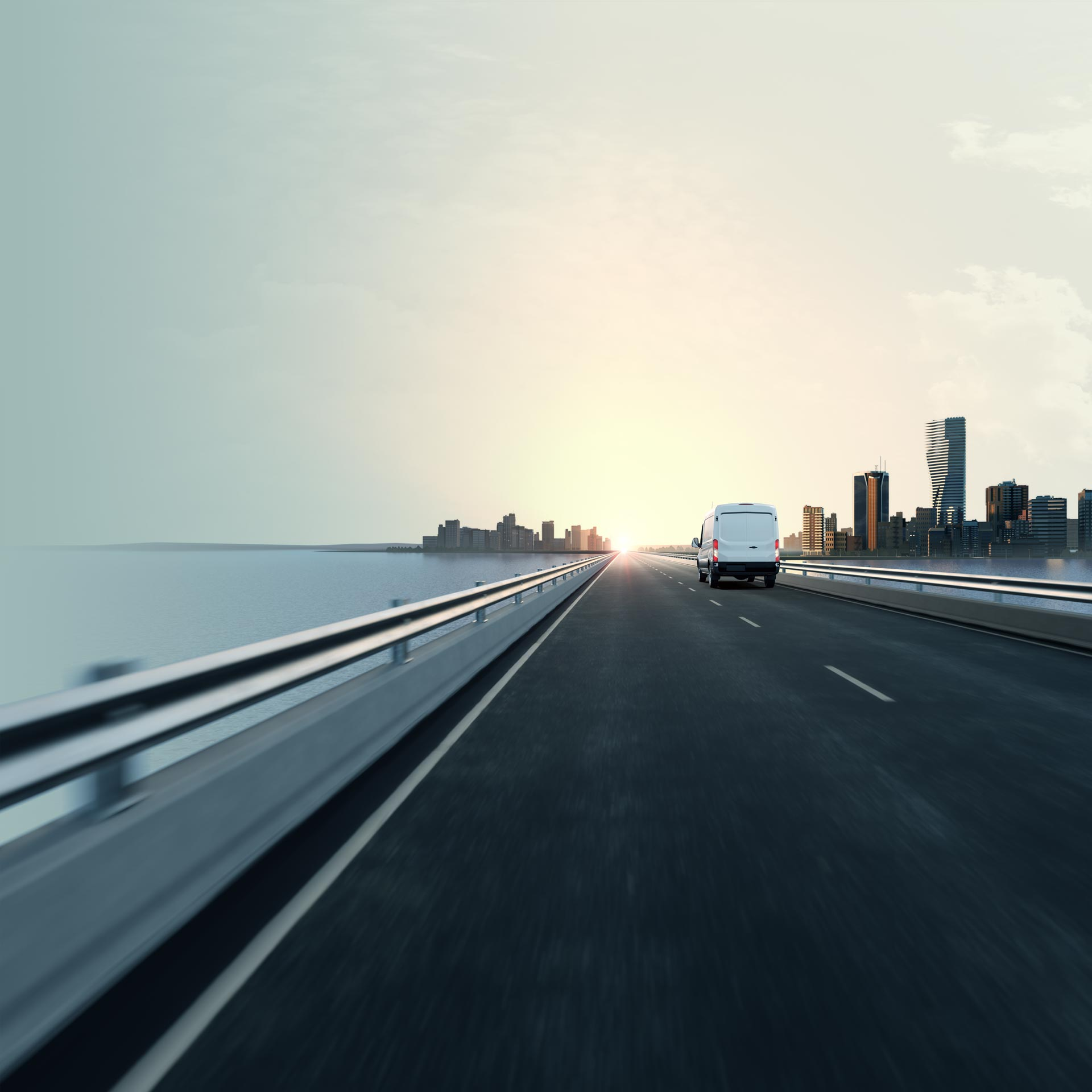 Semi-truck driving down highway toward city with sunrise