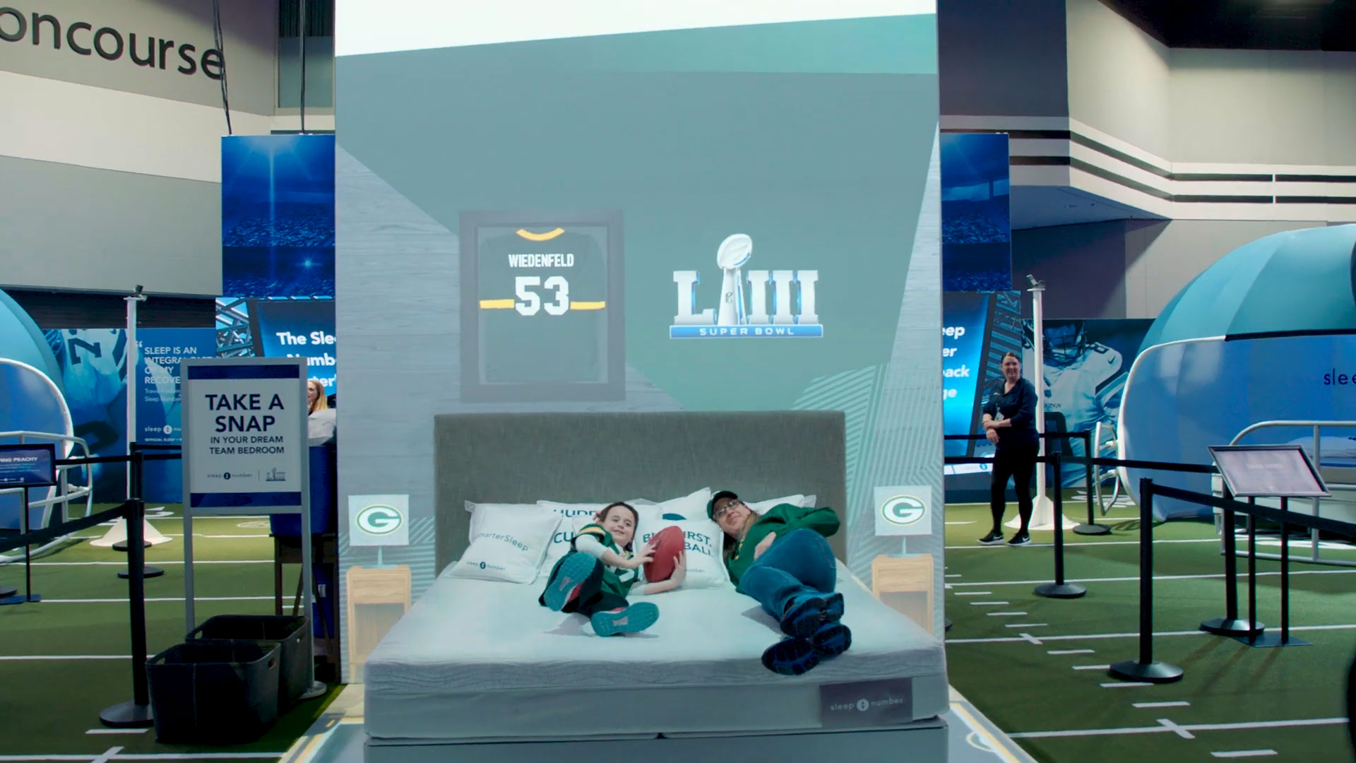 Woman and child lying on a Sleep Number bed in front of NFL projection display