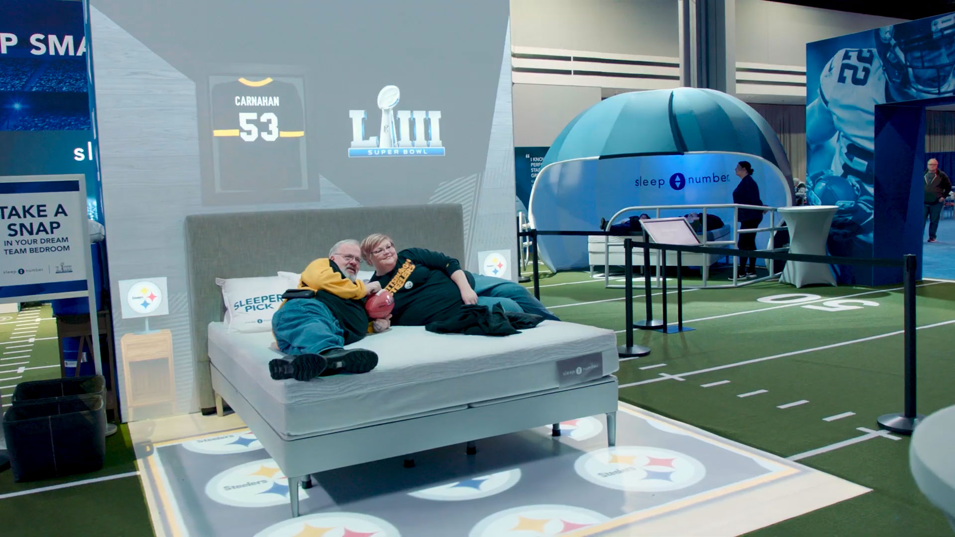 A man and woman laying on Sleep Number bed in front of Super Bowl projection