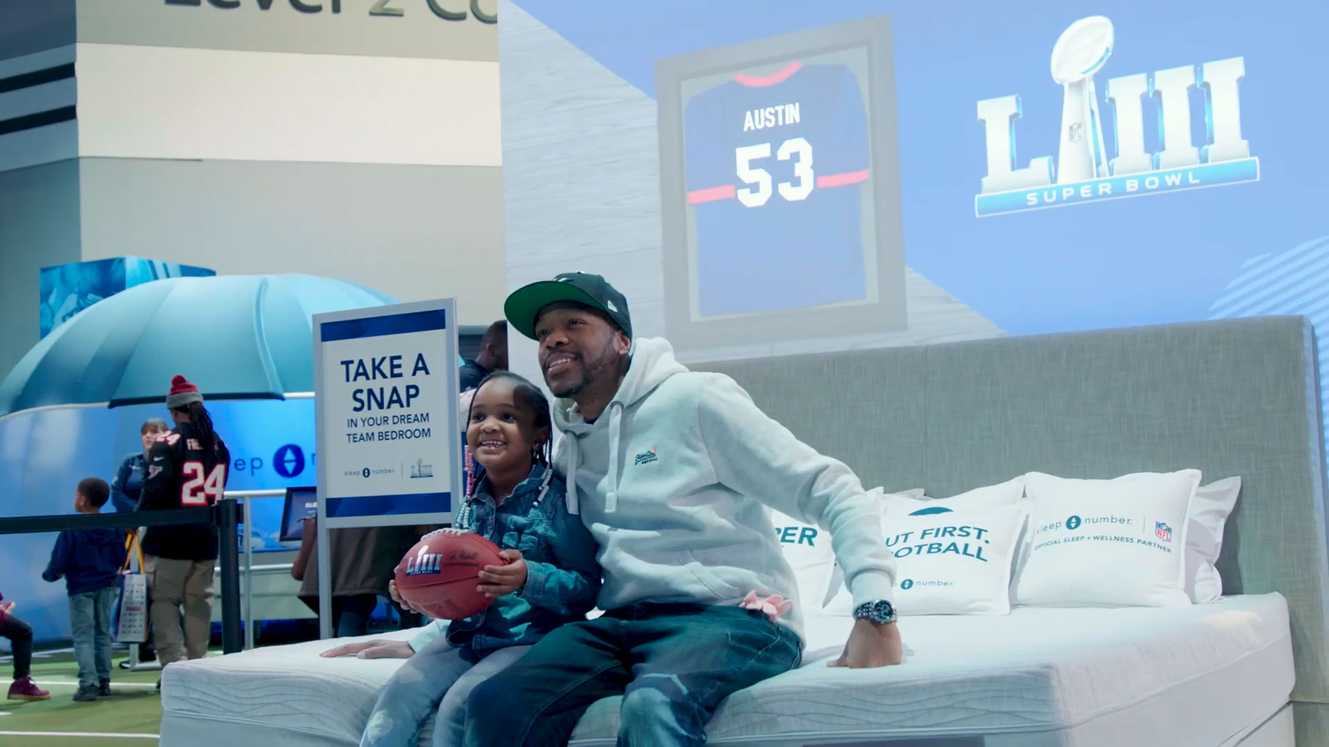 Man and daughter sitting on Sleep Number bed in front of NFL display