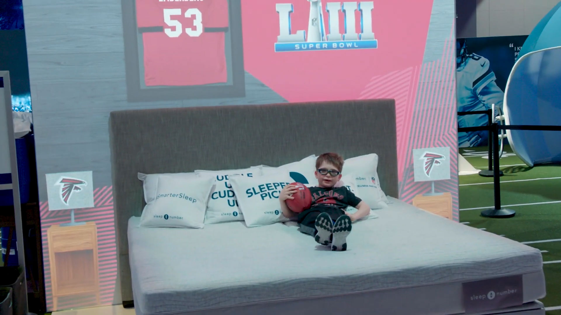 Young boy holding a football lying on a Sleep Number NFL display