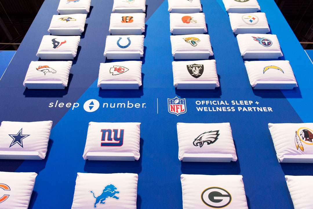 Miniature pillows with NFL team logos against blue Sleep Number display