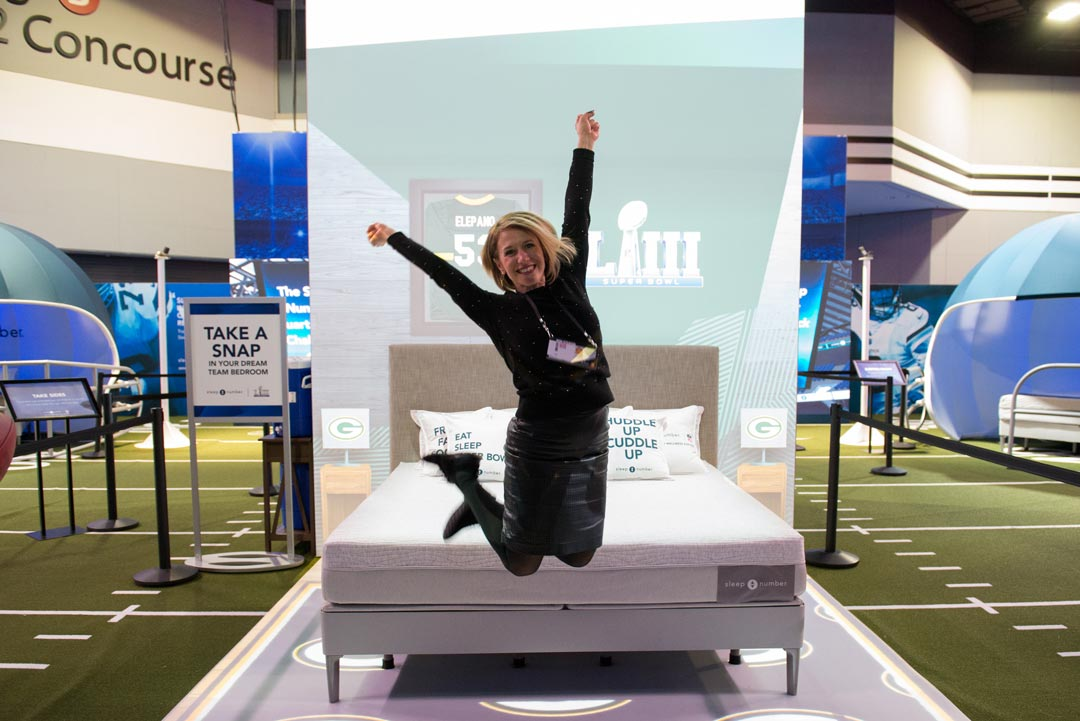 Woman jumping in the air in front of a Sleep Number Super Bowl display