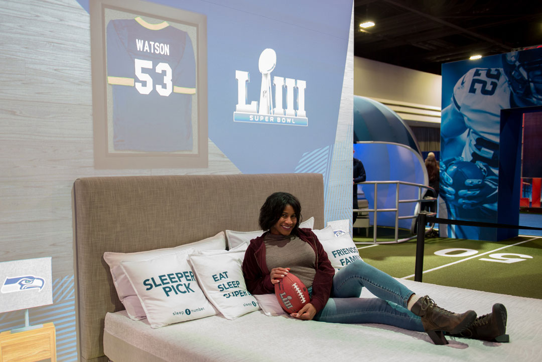 Woman laying on bed in front of Super Bowl NFL backdrop