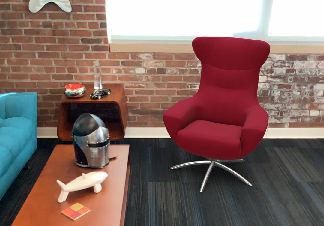 AR version of a red armchair in front of exposed brick wall in an office