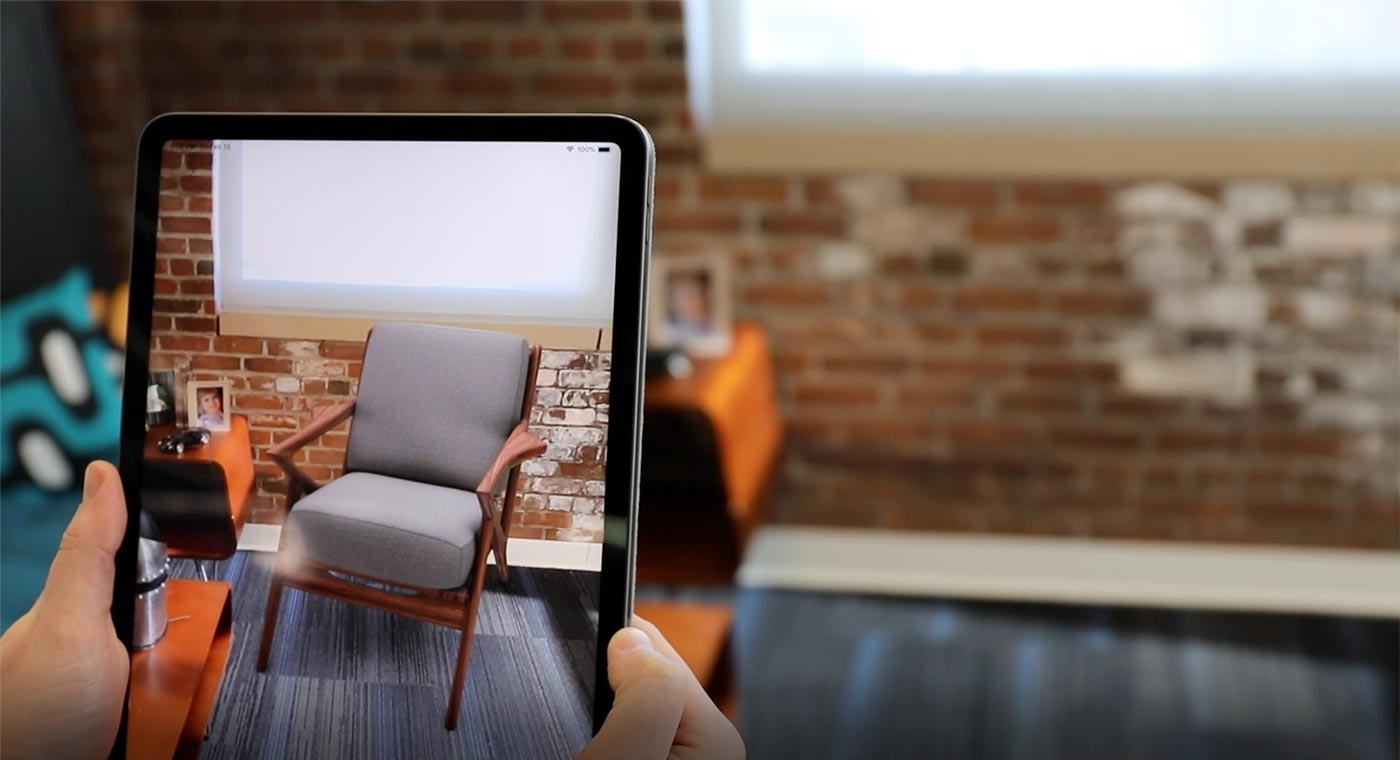 Hands holding iPad showing Furniture AR in office