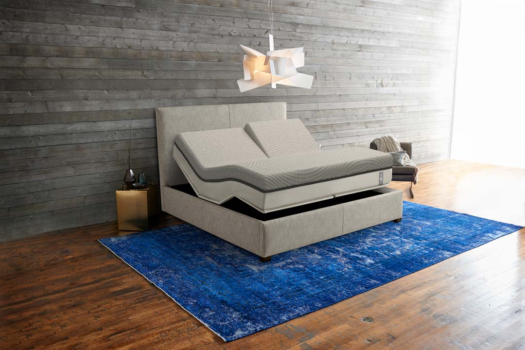 Flexible smart mattress in bedroom on a blue rug over wood floors
